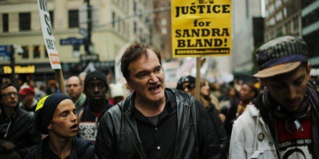 US film director Quentin Tarantino (C) takes part in a march against police brutality called 'Rise up...