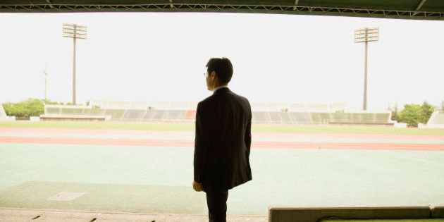 Soccer coach standing at stadium, rear