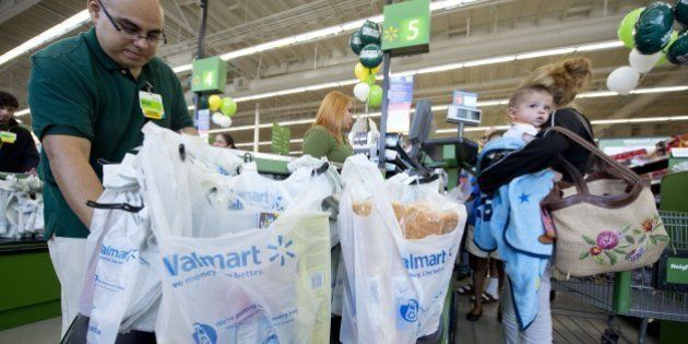 Customer service manager David Cuevas packs items into plastic shopping bags as a customer pays at the...