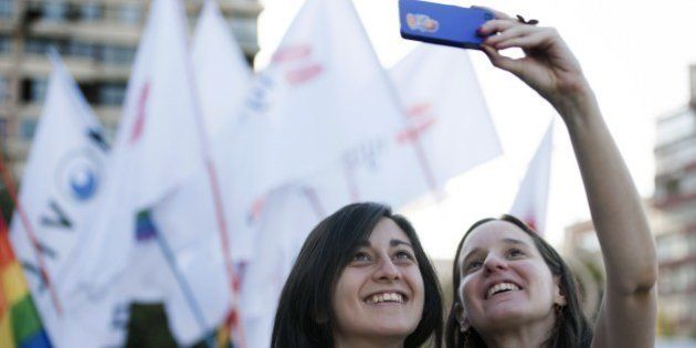 A couple takes a selfie during the celebration of the approval of the first law that would allow same-sex couples to enter into civil unions in Santiago on January 28, 2015. Congress on Wednesday approved -by a 78-9 vote margin- the country's first law authorizing civil unions of gay and lesbian couples. The law, which has been in the works for four years, gives legal recognition to unmarried couples and ensures their rights to receive pensions, enroll in health plans and inherit property from one another. AFP PHOTO/VLADIMIR RODAS (Photo credit should read VLADIMIR RODAS/AFP/Getty Images)