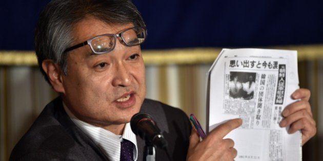 Former reporter with Japanese newspaper Asahi Shimbun, Takashi Uemura, displays a copy of an article...
