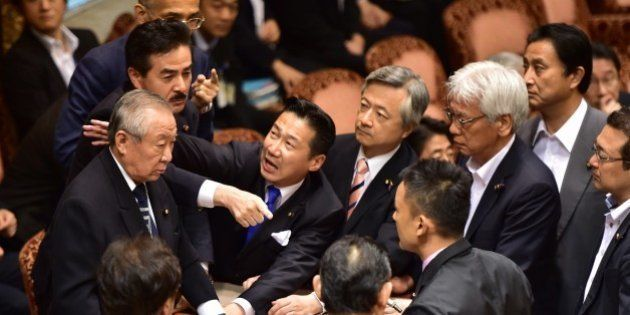 Opposition lawmakers surround chairman Yoshitada Konoike (L) as lawmaker Masahisa Sato (2nd L) gestures...