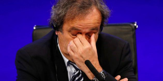FILE - In this May 24, 2013 file photo UEFA President Michel Platini reacts as he speaks to members of...