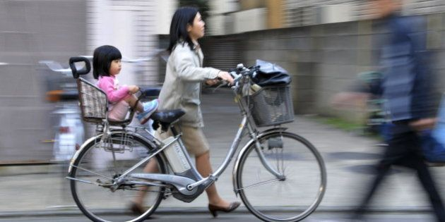 JAPAN-EDUCATION-SOCIETY-CHILDREN, FEATURE, BY MIWA SUZUKI A mother pushes her bicycle carrying her daughter...