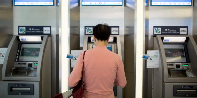 A woman uses an automated teller machine (ATM) inside a Standard Chartered Plc bank branch in Hong Kong,...
