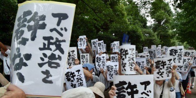 Protesters display placards during an anti-government rally outside the National Diet in Tokyo on July...