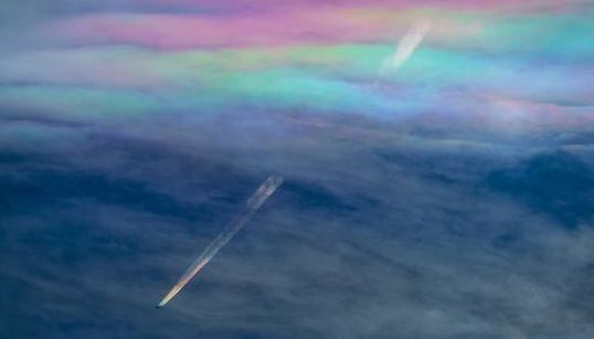 虹色の飛行機雲が、虹色の「彩雲」をくぐり抜ける(画像)