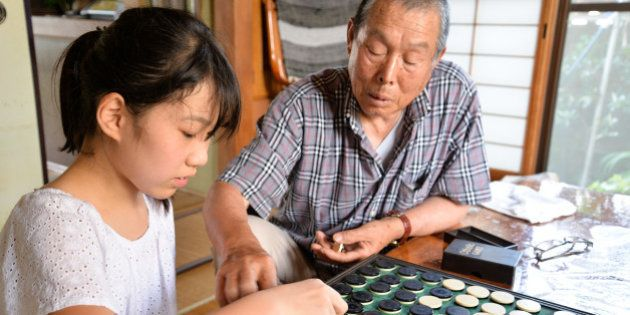 Granddaughter and grandfather playing Othello / Reversi, in cozy Japanese