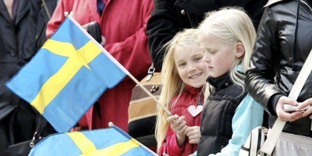 STOCKHOLM, SWEDEN - APRIL 30: Young girls wave Swedish flags during the changing of the guard on H.M....