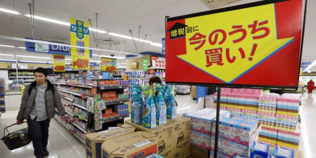 Signage displays sale prices as customers shop at a Seiyu GK supermarket, a discount chain owned by Wal-Mart...
