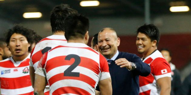 Japan's coach Eddie Jones talks with his players after the Rugby World Cup Pool B match between USA...