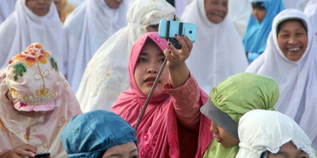 An Indonesian Muslim woman adjusts a selfie stick as she prepares to take a selfie during Eid al-Fitr...