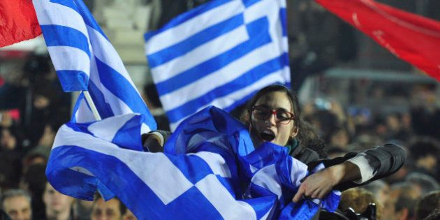 A woman waves a Greek flag during a speech by the leader of Syriza left-wing party Alexis Tsipras outside...