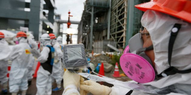 A worker wearing protective clothing and mask measures the radiation in the air as employees prepare...