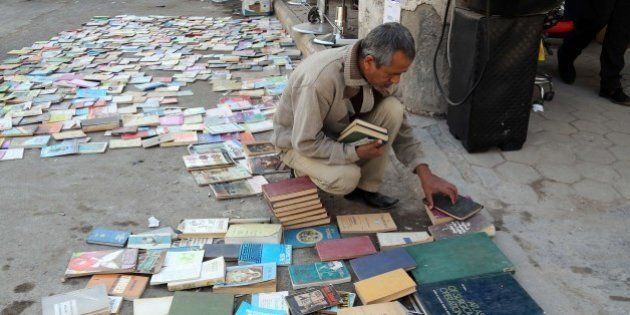 In this Friday, Jan. 23, 2015 photo, an Iraqi man looks at books on al-Mutanabi Street, home to the city's...