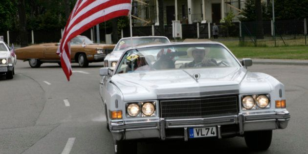 A Cadillac with a U.S. flag is seen during an American car owners' meeting in Jurmala, about 20 km from...