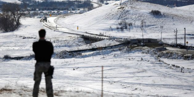 A police officer monitors the outskirts of the Dakota Access oil pipeline protest camp near Cannon Ball,...