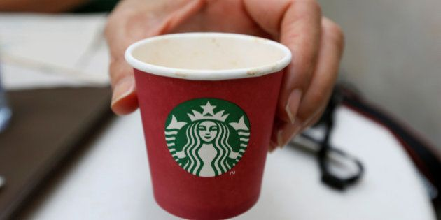 A woman displays a red Starbucks cup at a Starbucks cafe in Beirut, Lebanon November 20, 2016. Picture...