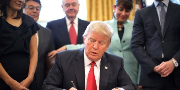 U.S. President Donald Trump signs an executive order cutting regulations, accompanied by small business...