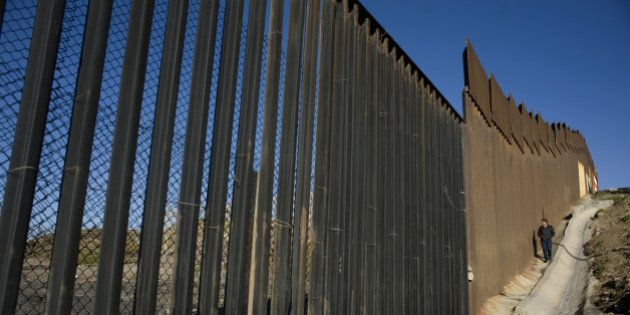 A person walks along a section of the U.S.-Mexico border wall in Tijuana, Mexico, on Thursday, Jan. 26,...