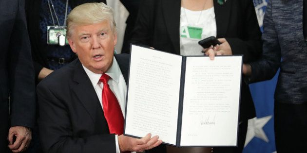 U.S. President Donald Trump, center, holds up a signed executive order at the Department of Homeland...
