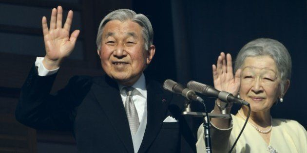 Japanese Emperor Akihito (L) and Empress Michiko (R) wave to well-wishers on the balcony of the Imperial...