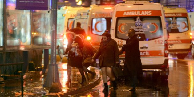 People flee as ambulances are on the attack site on January 1, 2017 in Istanbul. At least two people...