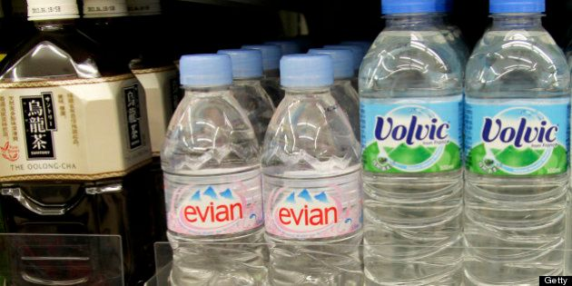 Bottles of Evian and Volvic water produced by Danone are displayed next to bottles of Suntory Holdings...
