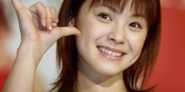 Japanese pop singer Aya Matsuura poses for photographers during apromotion event in Taipei May 13, 2002....