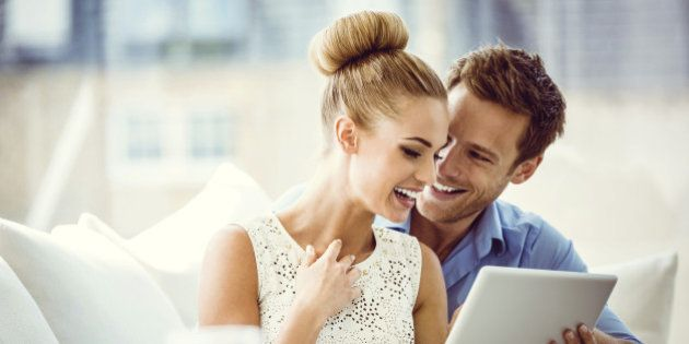 Portrait of happy couple sitting on sofa at home and using a digital