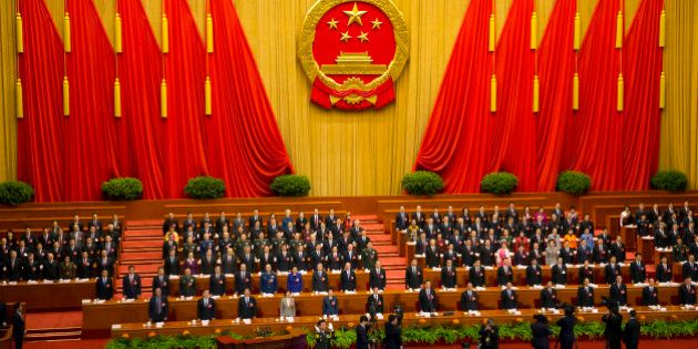 China's top leaders stand as they sing the national anthem during the opening session of the annual National...