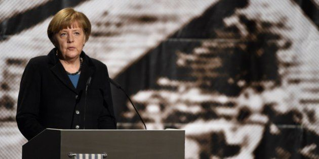 German Chancellor Angela Merkel stands in front of an historic picture of the Auschwitz concentration...