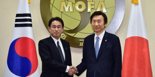 South Korean Foreign Minister Yun Byung-Se, right, and his Japanese counterpart Fumio Kishida pose for...