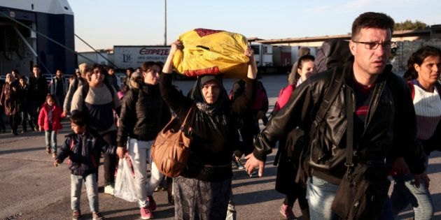 Migrants and refugees disembark from a ferry after their arrival from the Greek island of Lesbos at the...