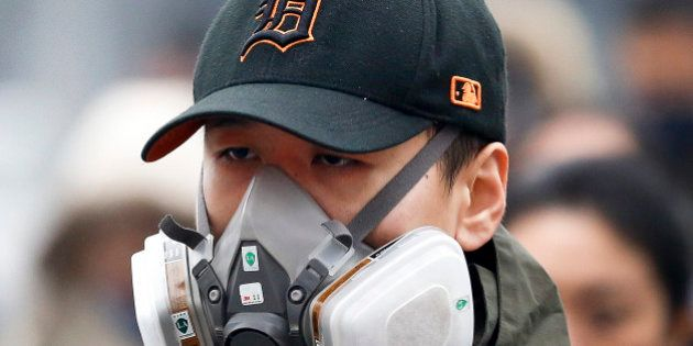 In this Dec. 8, 2015 photo, a man wears a mask to protect himself from pollutants on a heavily polluted...