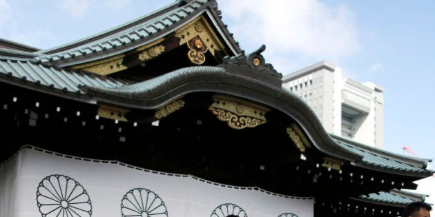 Visitors wipe their faces after offering prayers to the war dead at the Yasukuni Shrine in Tokyo, Saturday,...
