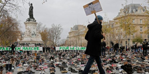 A man walks between shoes as hundreds of pairs of shoes are displayed at the place de la Republique,...