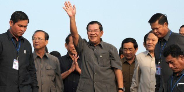 Cambodian Prime Minister Hun Sen (C) greets people during a ceremony for casting concrete to connect...