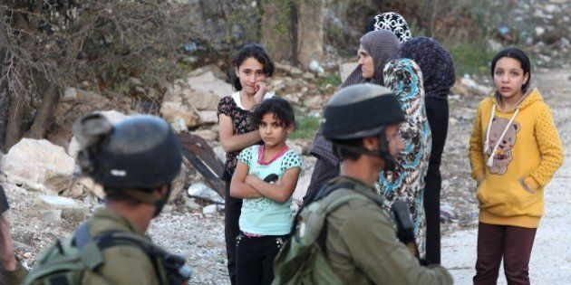 Israeli security forces stand and Palestinians gather at the scene where a Palestinian attempted to stab...