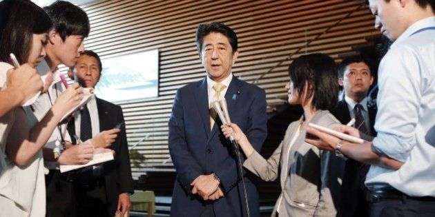 Japan's Prime Minister Shinzo Abe (C) is surrounded by reporters as he speaks at his official residence...