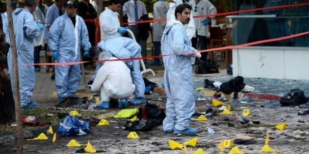 Turkish forensic investigators work at the site of a suicide bombing which killed at least 31 on July...