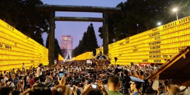 A portable shrine is carried past rows of lit lanterns during the Mitama Matsuri festival at the Yasukuni...