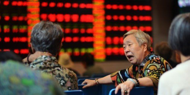 A stock investor reacts in front of a screen showing stock market movements in a brokerage house in Shanghai...