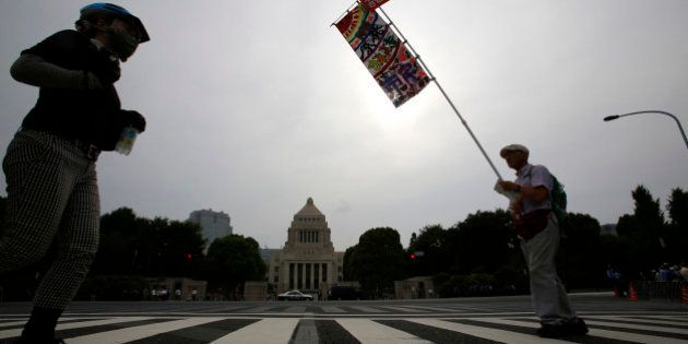 A protester holds a banner in front of the National Diet building during a rally in Tokyo, Sunday, June...