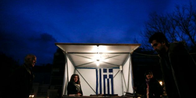 A Greek flag is seen inside a kiosk of the New Democracy party, as people walk by in Athens on Tuesday,...