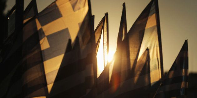 ATHENS, GREECE - JULY 05: The sun sets through Grrek flags over the Greek parliament as the polls have...