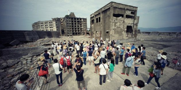In this June 29, 2015 photo, tourists visit a part of Hashima Island, commonly known as Gunkanjima, which...