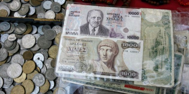 Old Greek drachma coins and notes sit arranged for sale during an antique bazaar at the northern port...