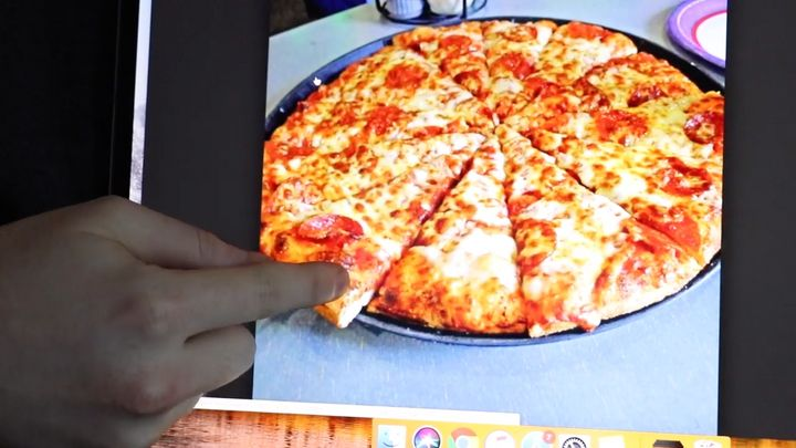 Shane Dawson points out the uneven pizza slices on his computer.