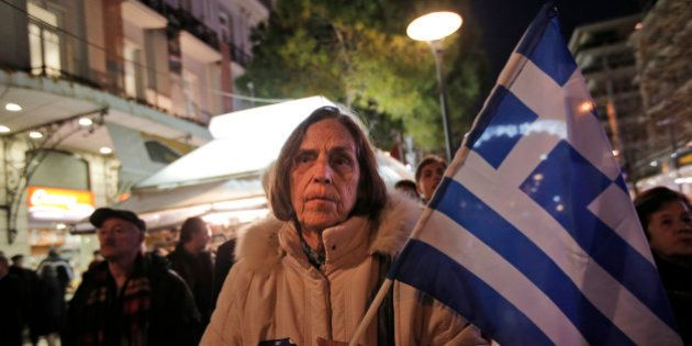 A supporter of Greece's conservative New Democracy party, holding the national flag, waits to greet the...